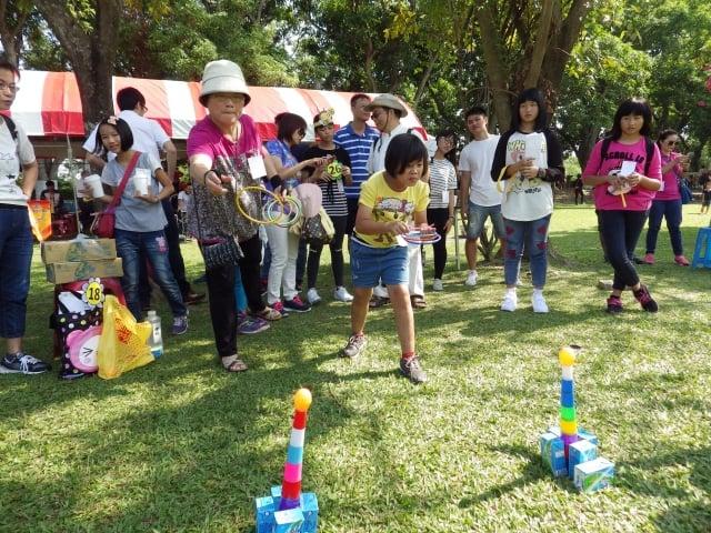 認養人帶著家人與認養童一起玩丟圈圈遊戲。