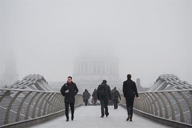 1月23日,濃霧籠罩倫敦,站在千禧橋上,不遠處的聖保羅大教堂只能看到一個模糊的輪廓。(Leon Neal/Getty Images)