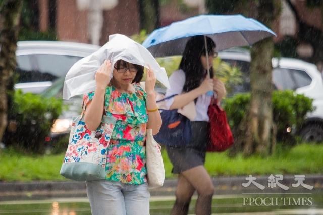 中央氣象局15日午後發布10縣市大雨特報。圖為台北街頭大雨,一位民眾以塑膠袋擋雨。(記者陳柏州/攝影)