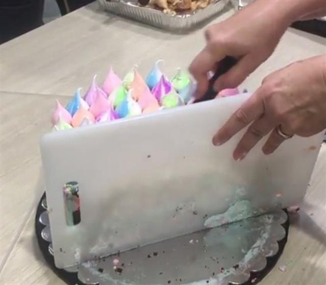 用砧板擋住蛋糕,順平行方向切下一條。(影片截圖)