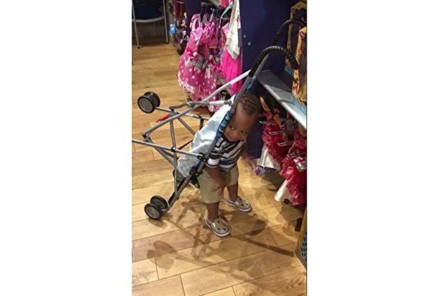 被父母固定在嬰兒車上的喬賽亞,看到喜歡的玩具,忘我地「背著嬰兒車」走了過去,舉起手來想去拿玩具。(臉書截圖)
