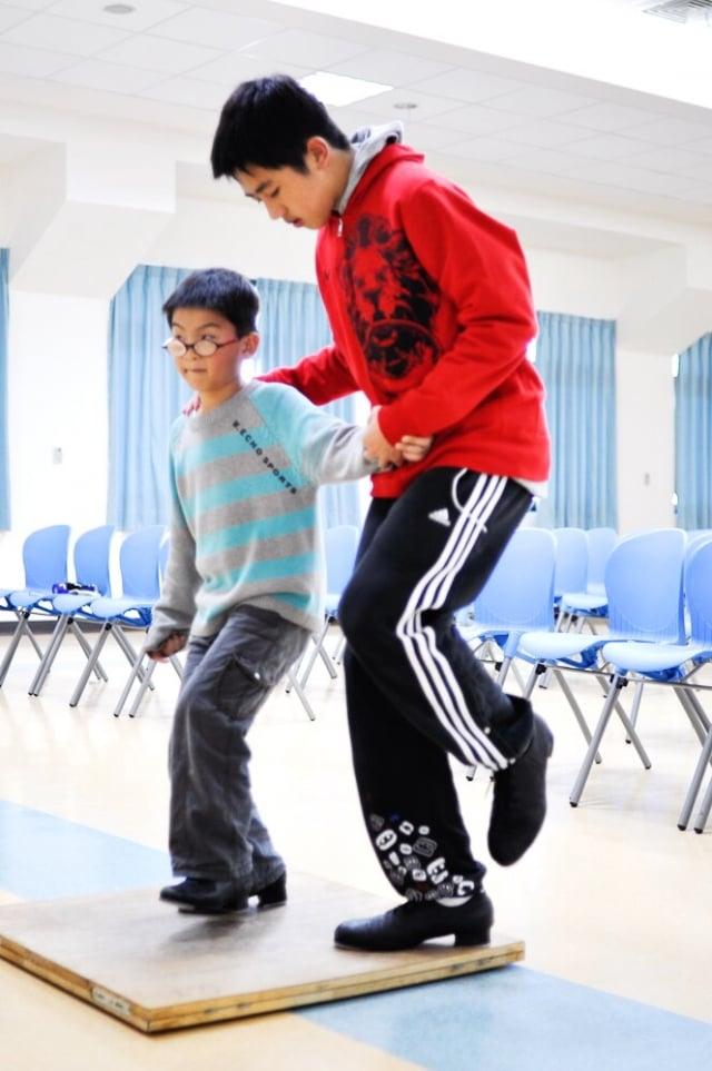 黃業棠在惠明盲校當志工,教導盲生跳踢踏舞。