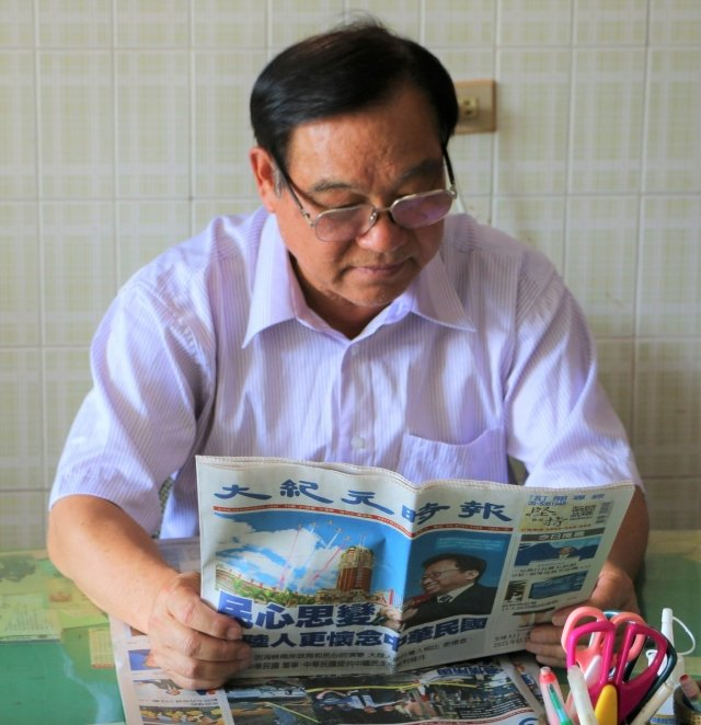 李丁紅先生平時看大紀元時報專注的神情。(吳雁門/攝影)