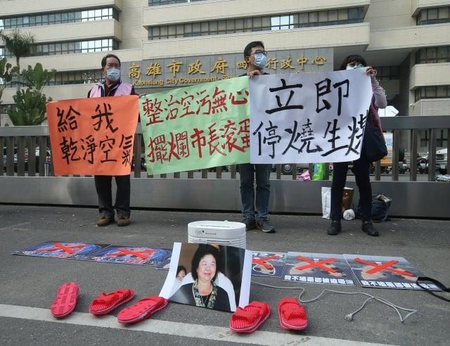 多名環保團體成員21日到高雄市政府前,針對空汙議題高舉海報標語等陳情抗議。(中央社)