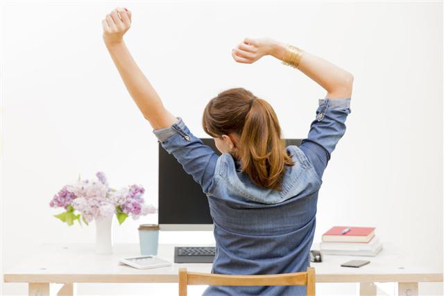 工作擠得滿滿時,要記得伸展手腳,站立走動,否則就會腰痠背痛。(Fotolia)