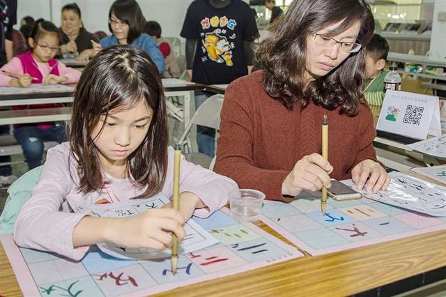 親子一起共學,練習毛筆字。(新唐人提供)
