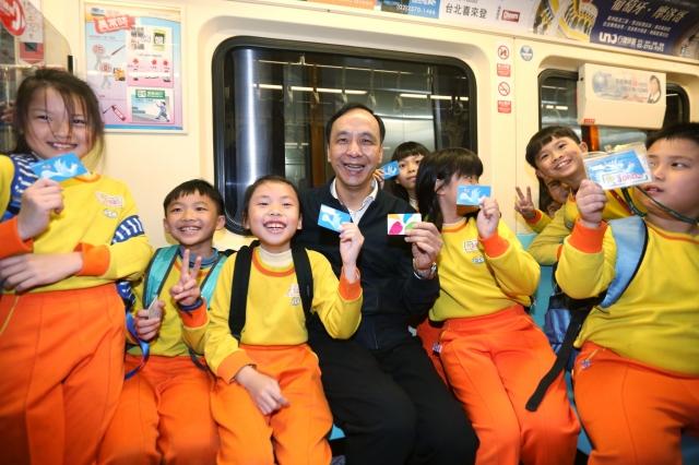 新北市長朱立倫陪同小朋友體驗搭乘北捷4折優惠。(新北市政府新聞局提供)