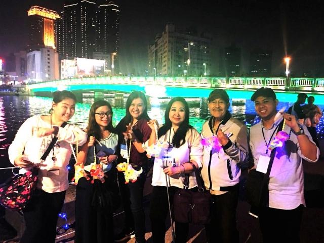 菲旅賓踩線團員開心提著「旺來狗」小提燈參觀2018年高雄燈會藝術節。(高雄市觀光局提供)
