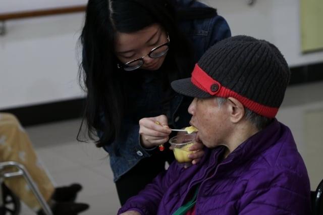 年輕志工餵長輩吃點心。