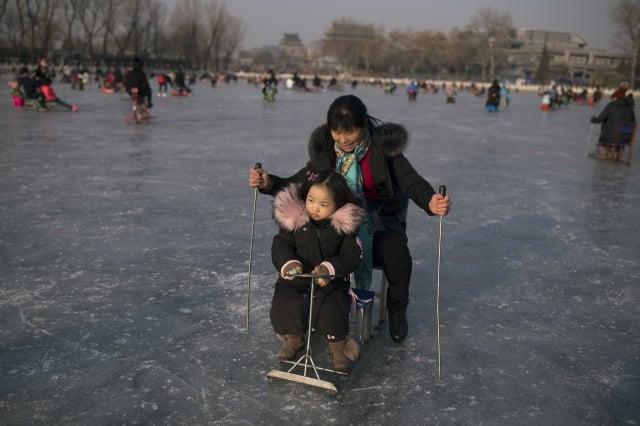 中國生二胎的家庭,讓越來越多的長男、長女陷入「同胞競爭障礙」。圖為一對中國母女在北京結冰的湖面上溜冰。(NICOLAS ASFOURI/AFP/Getty Images)