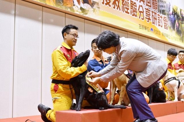 內政部部長葉俊榮頒發「英勇搜救胸章」給投入救災的搜救犬。(內政部提供)
