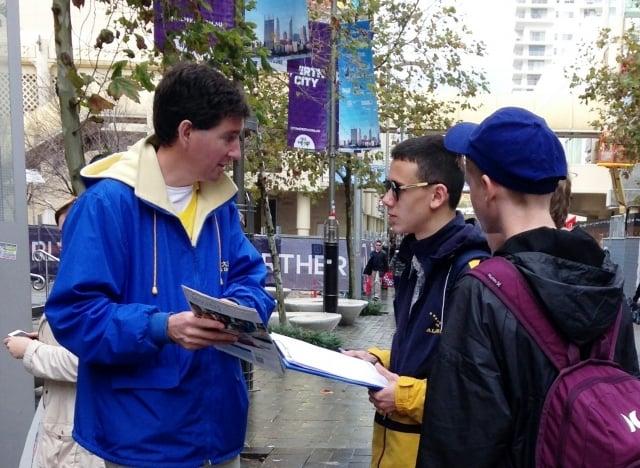 西澳企業家馬克.哈奇森(左)在街頭向民眾講述法輪功真相。(明慧網)