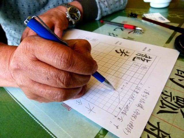 呂增興示範握筆手勢,也畫圖解說字的結構和規矩。(記者龍芳/攝影)