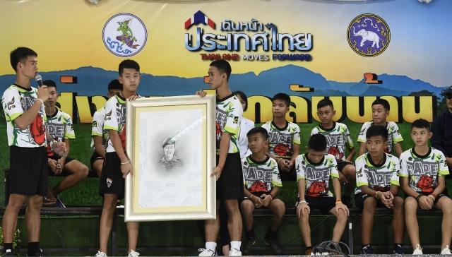 7月18日,泰國小足球隊教練Ekkapol Chantawong (左)和他的球隊成員,一起向為營救他們犧牲的泰國前海軍海豹突擊隊員致敬。(LILLIAN SUWANRUMPHA/AFP/Getty Images)