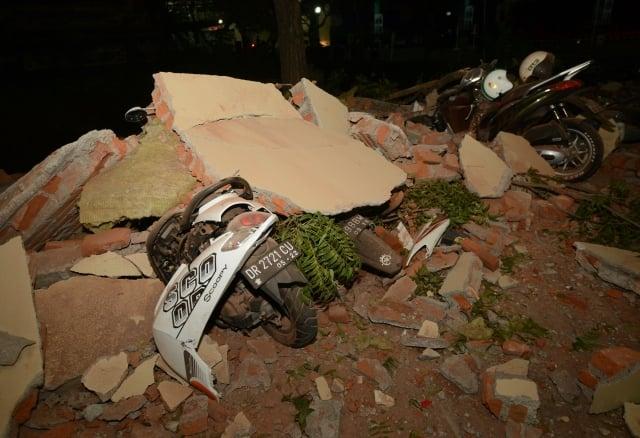 印尼8月5日發生規模6.9的地震,地點在龍目島附近,倒塌的石頭下是一輛摩托車殘骸。 (SONNY TUMBELAKA/AFP/Getty Images)