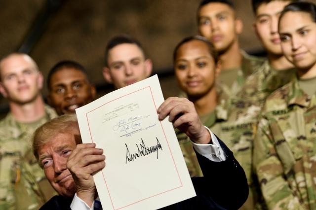 美國總統川普週一(8月13日)與副總統彭斯首次訪問紐約的Fort Drum軍事基地,並接見了第10山區師的士兵,川普還在現場簽署了2019年的《國防授權法案》。(Brendan Smialowski / AFP)