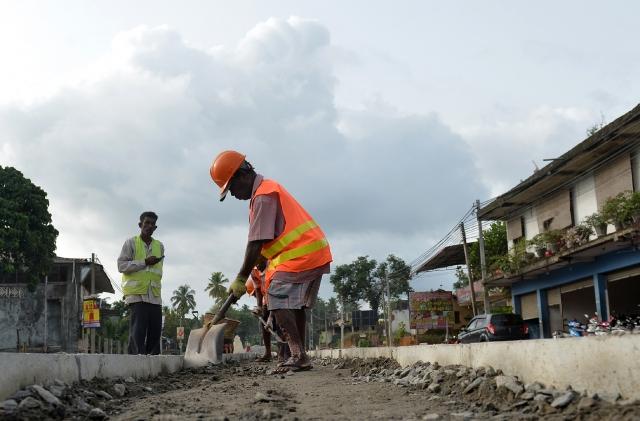 彭博指出,中共對外慷慨投資的計畫「一帶一路」,有可能重蹈前蘇聯覆轍的。圖為工人在斯里蘭卡可倫坡公路上施工。(Getty Images)