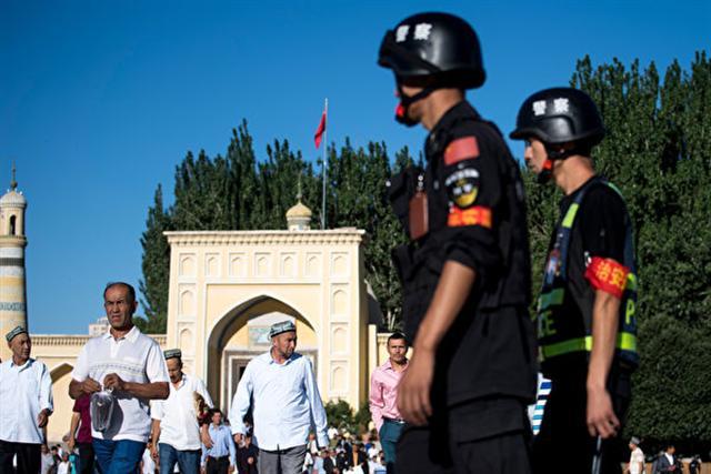 圖為2017年6月26日,警察在新疆喀什老城開齋節開幕後的清真寺巡邏。(JOHANNES EISELE/AFP)