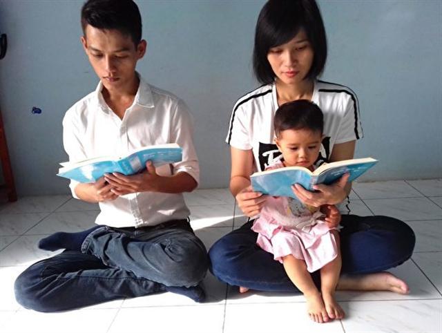 潘清海和妻兒在讀法輪大法書籍。(DKN.tv)