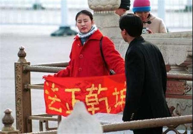 一名國內女法輪功學員拿著「法正乾坤」的橫幅在天安門和平請願,隨後遭到警方非法拘捕。美聯社圖片。(明慧網)