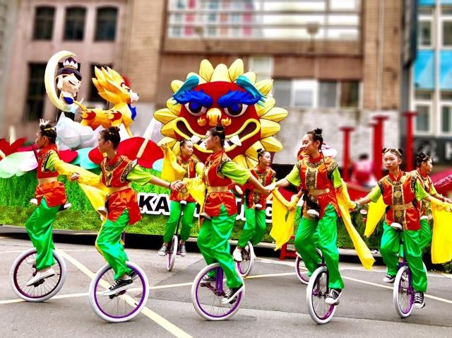 高雄國慶花車旁獨輪車表演,展現高雄囝子的青春活力。(高雄市觀光局提供)