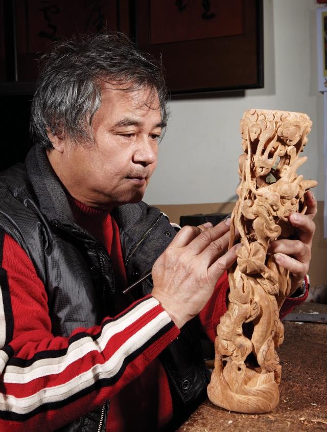 國寶級藝師李秉圭精心雕琢木雕作品。李秉圭是鹿港傳統木雕世家第五代傳人,傳承家族全方位小木作技藝。