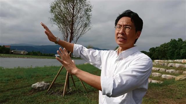 宜蘭大學土木工程系歐陽慧濤教授在分洪堰附近的溪畔說明河川整治的前後景況與影響。(攝影/陳祈心)