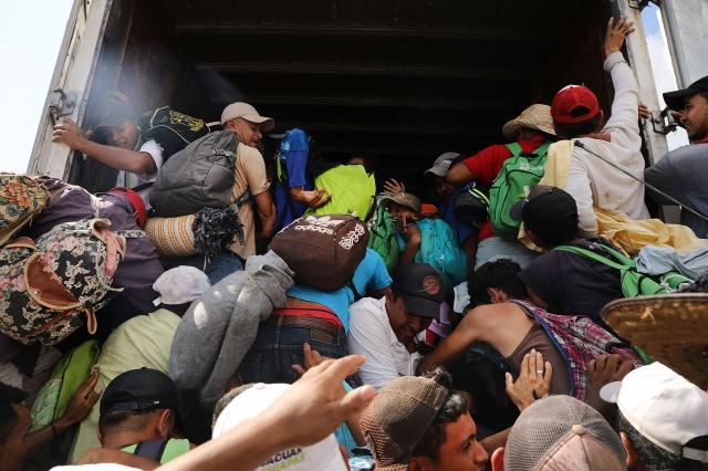 大蓬車隊移民11月3日拚命地朝著美國邊境移動,數十名兒童和成人擠進一輛貨櫃車。(Getty Images)