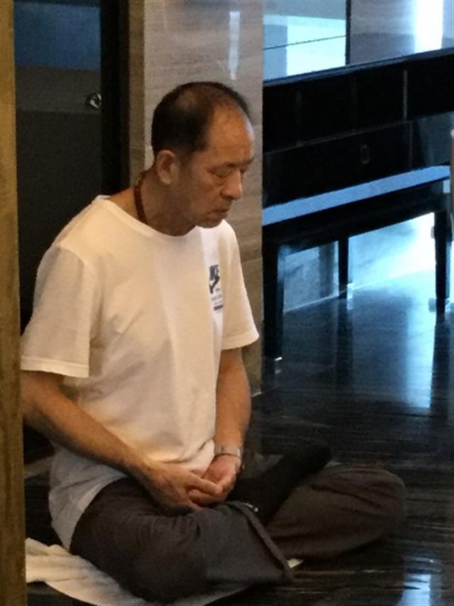 2016年8月6日護照被中共海關剪掉的那一天,王治文獨自打坐,女兒一旁傷心落淚,感到父親在中國是那麼孤獨。女兒說父親只是一個與世無爭的老人。(王曉丹提供)