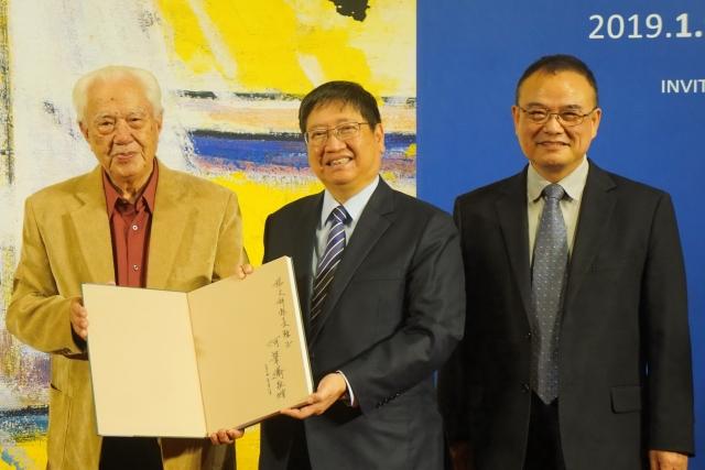 畫家何肇衢(左)贈送簽名畫冊給新竹縣長楊文科(中)