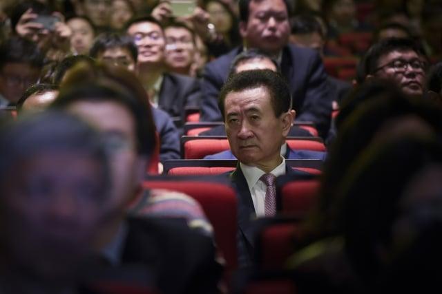 報導指出,過去1年半萬達透過甩賣資產進帳超過1,300億元人民幣。圖為萬達集團董事長王健林(中)。(AFP)