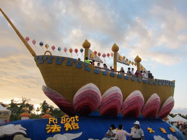 """「法船」花燈,船長25米、寬8米,底部是2米高的雲層,船桅上有""""真、善、忍""""3面令旗迎風飄揚,大法船看似騰飛在雲層上,充滿祥瑞之氣。"""