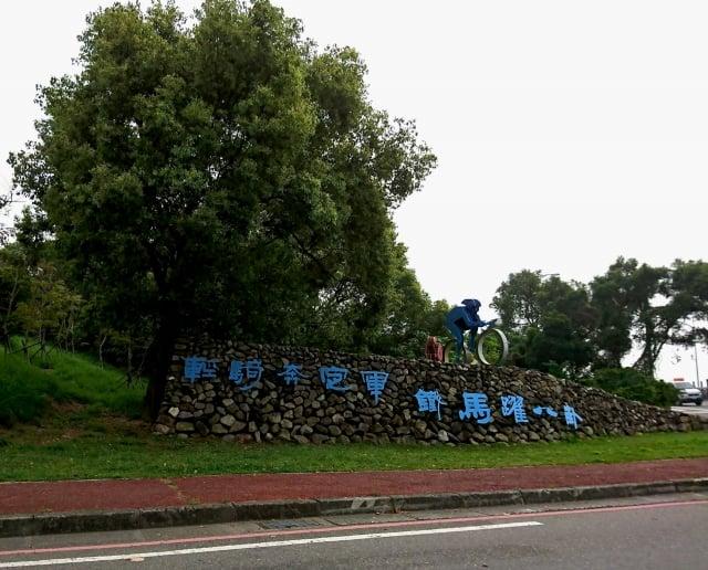 139縣道往南投方向有一處鮮明的藝術造景,一個騎著自行車的立體人形出現在一道鵝卵石砌的短牆上,石牆上寫著:「輕騎奔定軍、鐵馬躍八卦」。