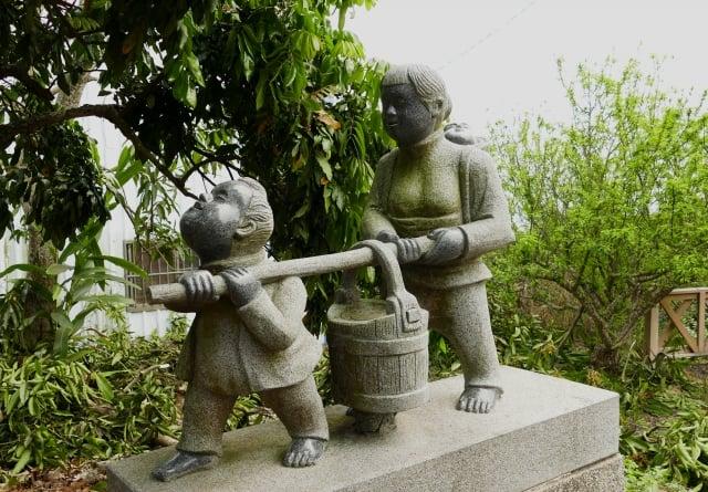 挑水古道入口的石雕像,一個小男孩與一名背著嬰孩的婦女共同挑著一個滿水的水桶,讓人想像挑水路途的苦楚。