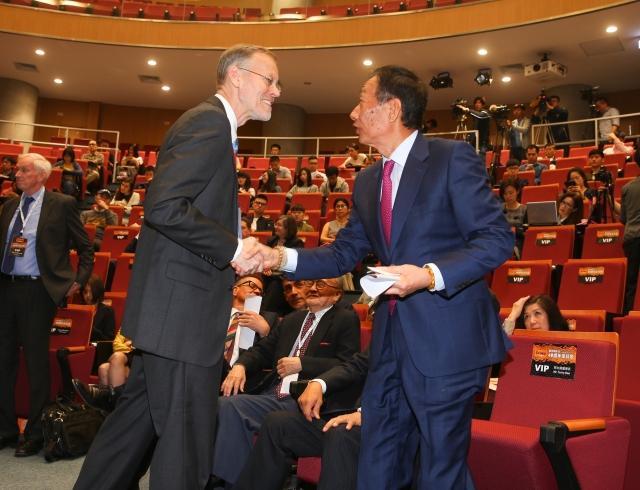 美國在台協會(AIT)處長酈英傑(Brent Christensen )(前左)15日出席「台灣關係法40週年座談會:台美根基與未來展望」,和鴻海集團總裁郭台銘(前右)握手致意。(中央社)