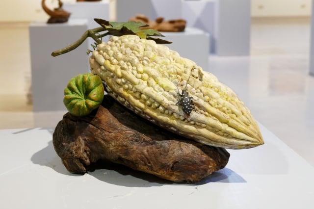 雕刻藝術家黃媽慶從匠師思維轉型藝術創作,他以苦瓜、佛手瓜、天牛鋪陳的「甘來」,即是動靜配合饒富情趣的作品。