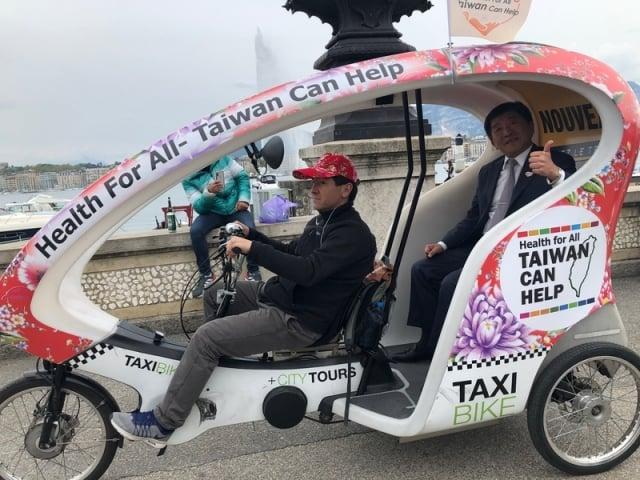 貼有台灣Health For All及Taiwan Can Help標語的觀光三輪車在日內瓦湖畔亮相,衛福部長陳時中(右)體驗搭乘。(中央社)