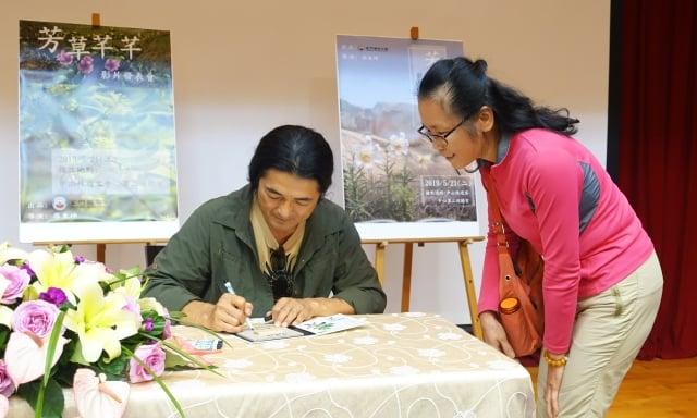 導演廖東坤(左)在首映發表會為觀眾簽名。