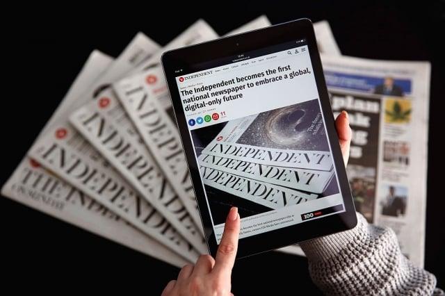 圖為2016年2月12日,在停止印刷前1個月的英國《星期日獨立報》,其網站顯示在iPad上,後面是印刷版報紙。(Dan Kitwood/Getty Images)