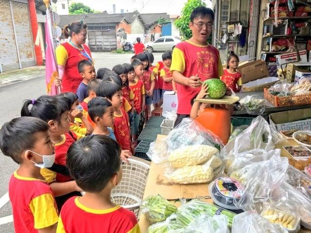 孩子拜訪老菜攤,學習蔬菜販賣的技巧。(楊雅婷提供)