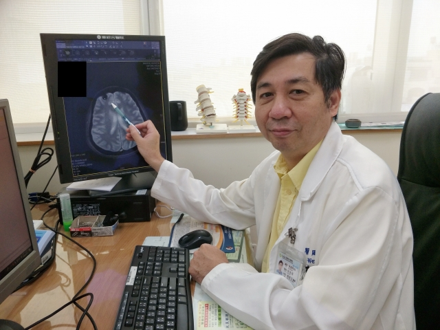 周啟文醫師以筆指出林姓女患者腦腫瘤位置。  (童綜合醫院提供)