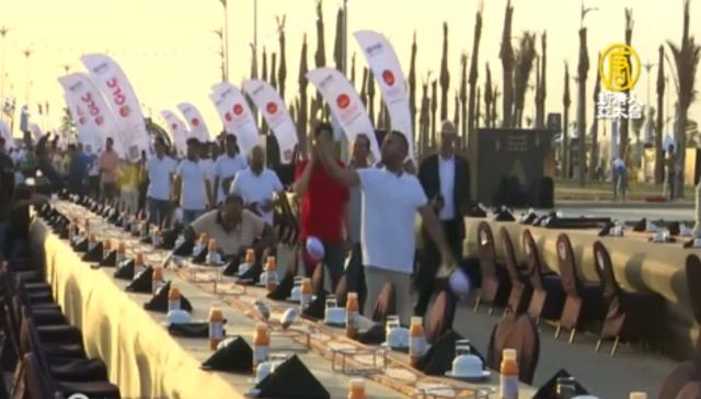 埃及新首都舉辦了開齋飯,擺設的桌子總長超過三千公尺,吸引七千名民眾參與。(新唐人電視台)