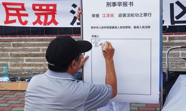 行政院金馬聯合服務中心執行長翁明志在舉報迫害法輪功元凶江澤民的刑事舉報書簽名。