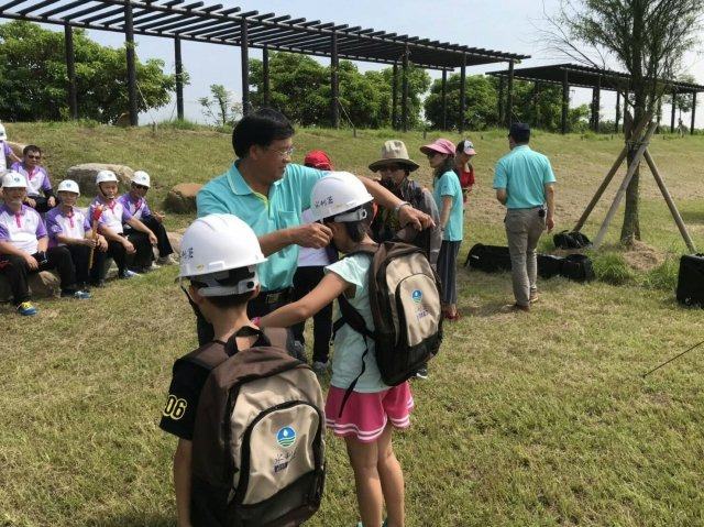 水利署第一河川局長陳健豐為小小志工戴上水利署巡查帽。(水利署第一河川局提供)