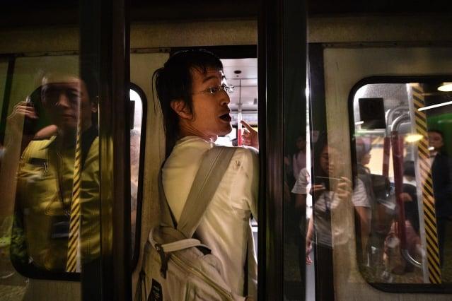 圖為示威民眾阻止地鐵車門關閉。 (Anthony WALLACE / AFP)