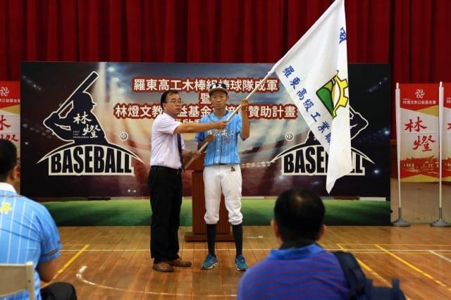 羅東高工廖俊仁校長(左)授旗給棒球隊。