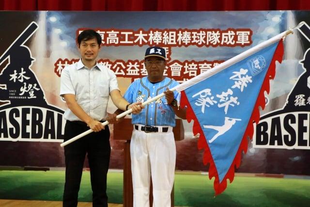 宜蘭縣政府教育處長王泓翔(左)授旗由教練陳瑞賢接受羅工棒球隊。