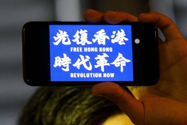 香港反送中抗議者使用名為「Bridgefy」的App,以反制中共的監控。圖為2019年8月23日,香港一名抗議者手持顯示有「光復香港時代革命」字樣的手機。( Anthony WALLACE / AFP)