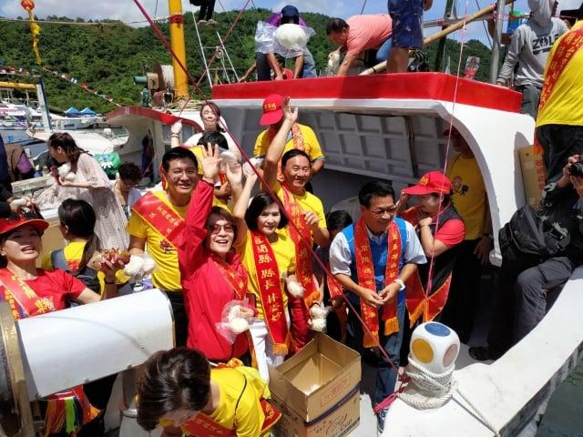 貴賓將包子等食物拋向空中,讓港邊的民眾一齊歡慶新船下水喜悅。