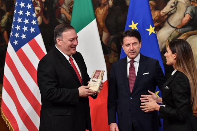 義大利女記者10月1日在義大利總理孔蒂(中)面前,贈送一包帕馬森乾酪給訪問羅馬的美國國務卿蓬佩奧(左)。( AFP/Getty Images)
